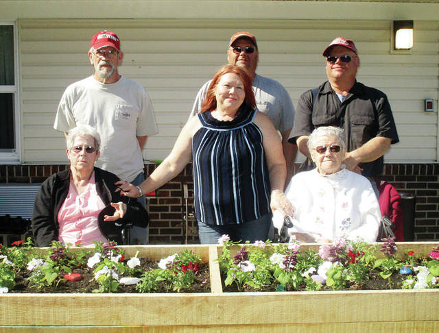A few residents of Heartland of Wauseon and their families worked to create a flower box and vegetable garden to allow Heartland residents the opportunity to garden during the dog days of summer. Lumber was donated by Garber's Saw Mill, owned by the sons of resident Catherine Garber. The box was put together by Jim Davis, nephew to resident Leona Loveland. The vegetable box is full of cucumbers, lettuce, peppers, and cherry tomatoes, while the flower box is full of annual blooms of all colors. Pictured - top, from left - is Jim Davis, Marty Garbers, Dave Garbers - bottom, from left - Heartland resident Leona Loveland, Stephanie Wallington of Heartland Activities and Central Supply, and Heartland resident Catherine Garbers.