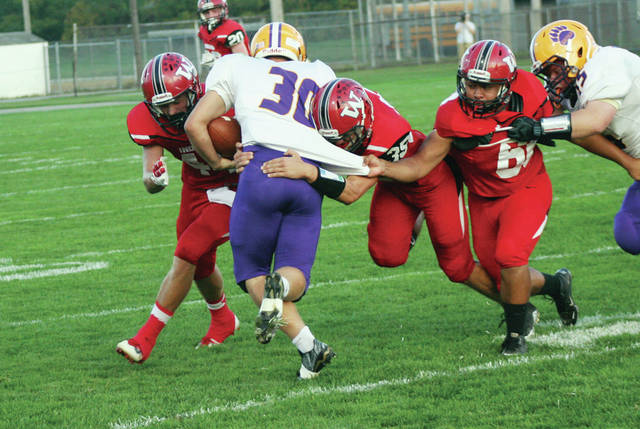Dawson Rupp, left, Joey Shema and Miguel Gomez of Wauseon all combine for a tackle on Bryan's Dominic James (30) during Friday's game. The Indians used a big second half run that included shutting out the Golden Bears 28-0 in the third quarter, to win by a final of 48-14.