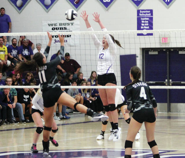 Swanton's Cydney Christensen (12) seals the win with a block of Otsego's Jaclyn Ghesquiere (11) Saturday in the Division III sectional final. The Bulldogs topped the Knights 17-25, 25-23, 25-23, 25-17.