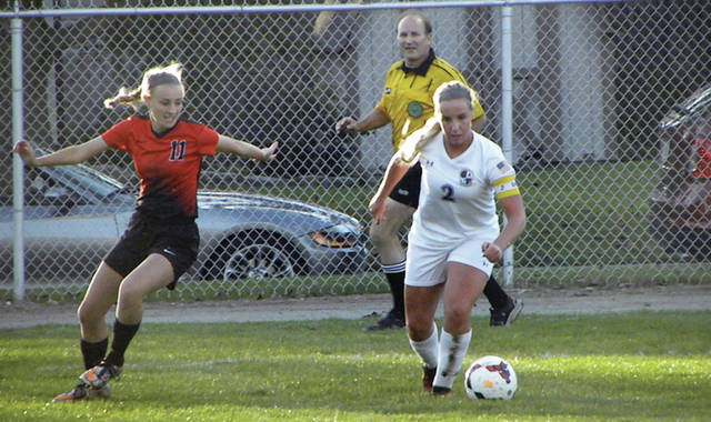 Emie Peterson of Archbold, right, handles the ball Wednesday against Cardinal Stritch in the Division III sectional final. The Blue Streaks were victorious by a final of 9-0.