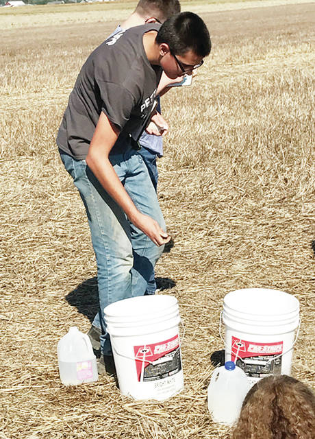 Pettisville FFA member Matt Rupp picks up soil from a bucket and judges its quality. FFA members participated in agronomy and soil competitions on Sept. 26.