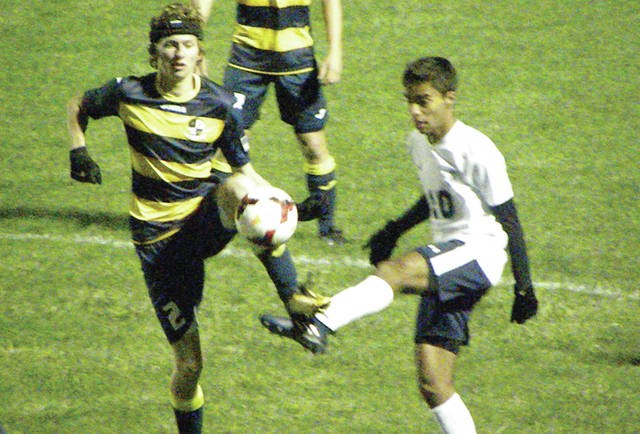 Luke McQuade of Archbold, left, plays a ball in the district semifinal against Maumee Valley Country Day Tuesday at Rossford. The Blue Streaks won by a 5-0 final.