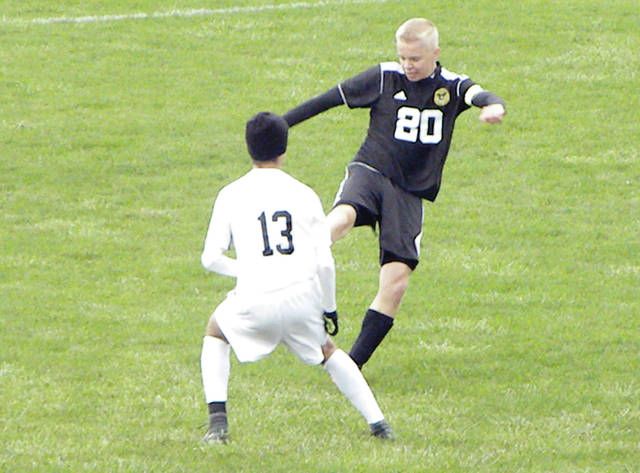 Pettisville's Landon Roth (20) kicks a ball with an Ottawa Hills player defending. The Blackbirds had their season come to a close after a 5-0 loss to the Green Bears in the Division III district semifinal Tuesday.