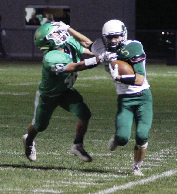 Hunter Van Wert of Evergreen tries to fight off the tackle of Darren Dunning of Delta with a stiff arm.