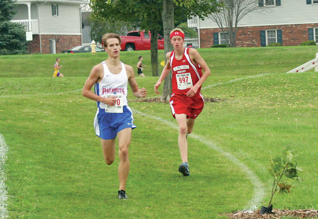Kyle Vernot of Wauseon, right, attempts to run down Nathan Bostelman of Patrick Henry at the NWOAL Cross Country Championships Saturday. However, he would finish third behind Liberty Center's Cameron Stark and Bostelman.