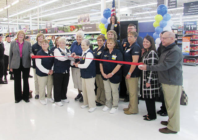 Wauseon Walmart manager Natasha Lockert, on platform, oversaw a ribbon-cutting ceremony Friday to celebrate the grand re-opening of the store following months of updates and renovations. The store features a refreshed bakery, check-out innovations, an expanded pharmacy, updated hardware apparel and infant departments, a revamped home lines area, and Electronics of the Future. Music was provided by the Wauseon High School Marching Band and A Cappela singers, and a VFW representative presented the store with a new flag. Pictured are select Walmart associates, Wauseon Mayor Kathy Huner, and Chamber of Commerce members including Executive Director Bill Drummer.