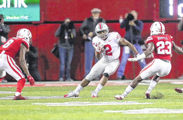 Ohio State running back J.K. Dobbins (2) makes a move on Nebraska defensive backs Chris Jones, left, and Dicaprio Bootle during the first quarter at Memorial Stadium on the campus of the University of Nebraska Oct. 14.