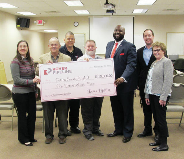Representatives from Rover Pipeline and its parent company, Energy Transfer, were on hand Tuesday in Napoleon to award $10,000 donations to the emergency management agencies of Fulton, Henry, and Defiance counties. Energy Transfer representative Alexis Daniel said the agencies may use the money to benefit the counties' first responders. Fulton County EMA Director Kelvin Freeman said the funds will be used to outfit an EMA truck and for emergency service projects. Pictured, from left, are: Daniel; Fulton County Commissioner Bill Rufenacht; Emergency Medical Services Director Robert DeLeon; Ohio Department of Transportation representative Mike Fountain; Freeman; Bill Barth, Energy Transfer Senior Specialist for Emergency Response; and Susan King, Rover Pipeline Community Outreach.