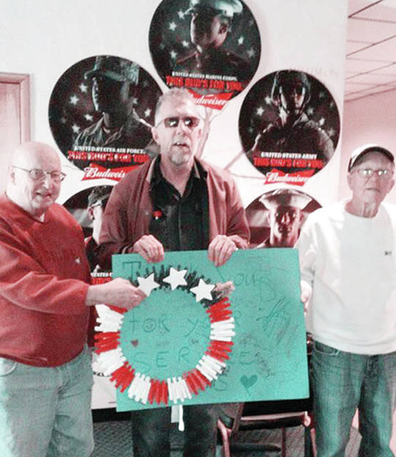 Ward Short, center, a Triangular Processing employee, helped make a red, white, and blue wreath for the veterans of the local VFW. Burt Lutz, left, and Marc Stoll are veterans who accepted the gift from Ward, and presented him with a T-shirt in exchange for his gift.