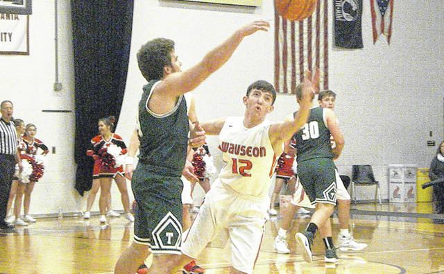 Wauseon's Trent Armstrong (12) defends a Tinora pass during the final of the Vision Chrysler Holiday Classic Thursday night. The Indians won the tournament with a 40-19 victory over the Rams.