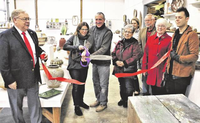 John Thies and Tiffany Hyland, cut the ribbon to open Oak Openings Pottery outside of Swanton.
