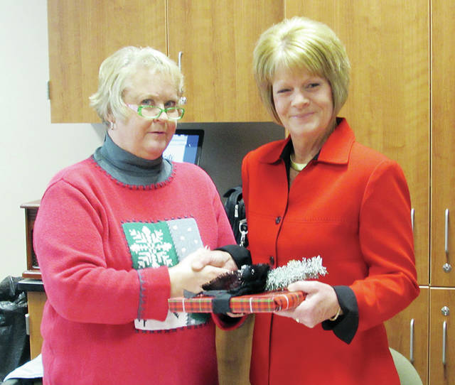Wauseon Board of Education President Sandra Griggs, left, presented departing board member Miriam Frank with a gift at Monday's meeting for her years of service. New board member Amy Fisher will take the seat in January.