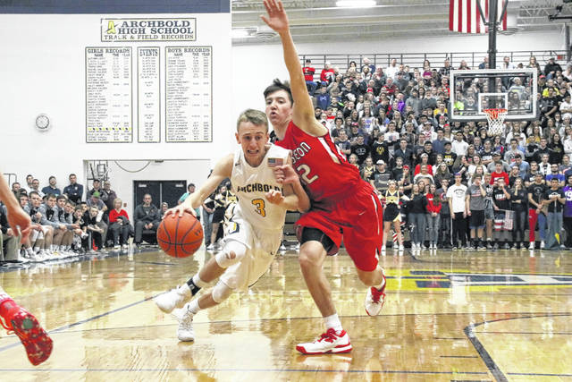 Eli Miller of Archbold, left, drives to the basket as Trent Armstrong defends for Wauseon. The Indians would defeat the Blue Streaks by a final of 67-56.