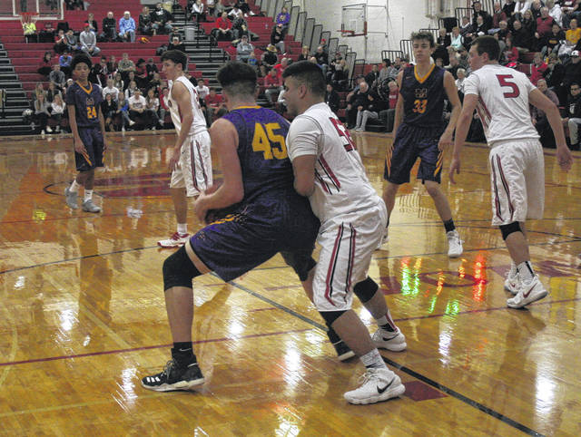 Wauseon's Trevor Rodriguez, right, looks to outmuscle Garret White of Maumee (45) during Tuesday's non-league matchup. The Indians ran away with an 80-35 victory over the Panthers.