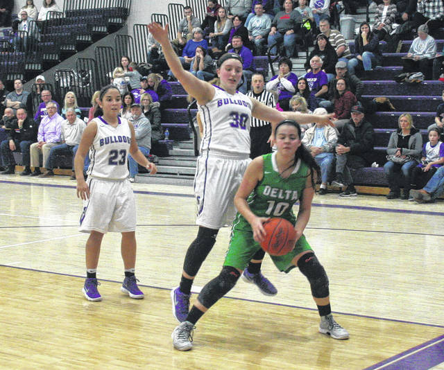 Delta's Brooklyn Green works the ball along the baseline as Sidney Taylor (30) defends for Swanton. The Panthers held on to defeat the Bulldogs in a pivotal NWOAL match-up, 43-41.