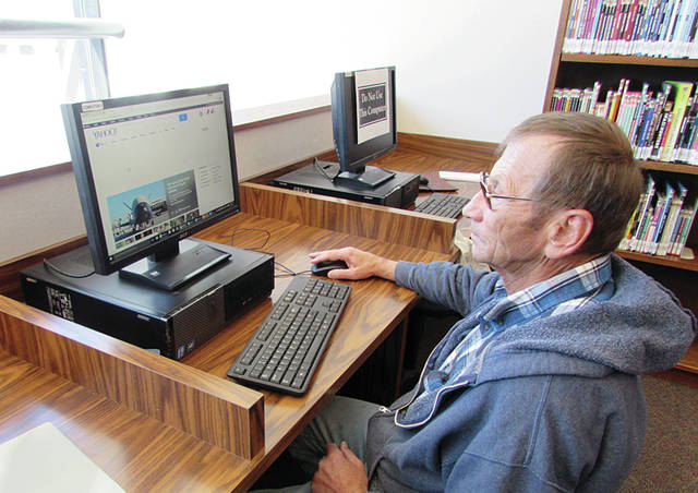 A. J. Borkowski of Wauseon uses a library computer as light pours into the facility's new glass entrance.