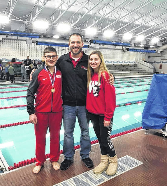 Wauseon divers Tony Schweinhagen, left, and Kennedy Nation, right, pose for a photo with their coach Tom Burkholder after competing in the Division II district diving meet Wednesday. Both have advanced to state, with Schweinhagen winning the boys competition and Nation taking 10th on the girls side.