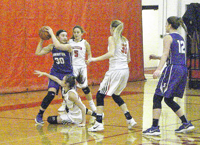 Sidney Taylor of Swanton (30) looks to get away from a swarm of Wauseon defenders Thursday during an NWOAL girls basketball game. The Bulldogs would defeat the Indians 59-42.