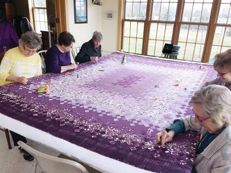"""Working on the 2018 Friendship Days Quilt, a """"Nine Patch Pattern"""" quilt to be raffled off, are, clockwise, Luann Goertzen, Suzie Schrock, Char Roth, Nancy Roth, and Esther Rupp."""