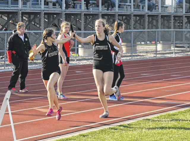 Nichole Foor of Pettisville, right, hands the baton to Elizabeth Sauder in the distance medley at the Archbold Walker/Dilbone Relays a few weeks ago. Foor and Sauder each won a pair of events this past weekend at the BBC Championships.