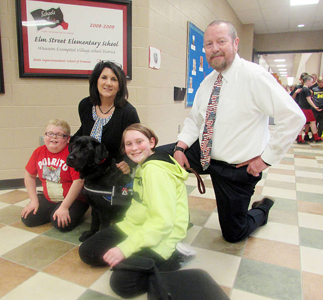 Oakley poses with, from left, third-grader Marcus Ward, elementary school principal Theresa Vietmeier, sixth-grader Ida Overmyer, and middle school principal Joe Friess.