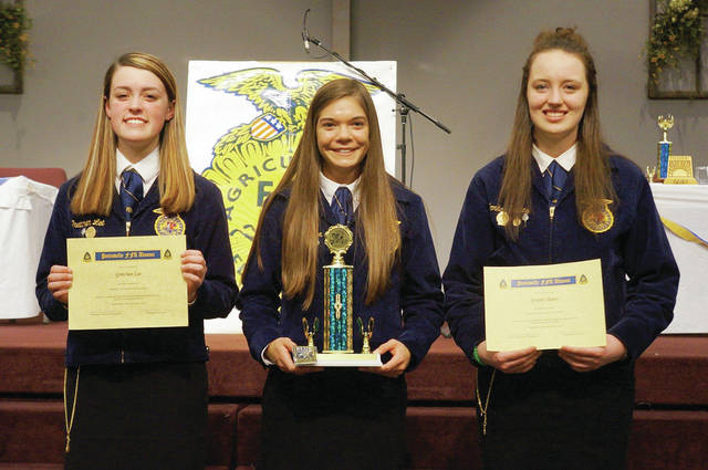 Gretchen Lee, Elizabeth Sauder, and Jordan Skates present their scholarship awards. Lee and Skates won scholarships from the FFA Alumni for ag-related college work next year, and Sauder won the Scholar Award for having a 4.0 GPA, the highest of all members.