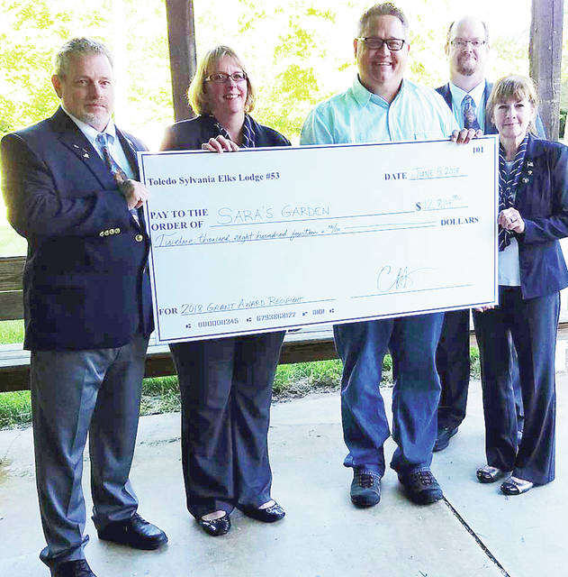 Toledo-Sylvania Elks Lodge Exalted Ruler Terry Harrison, far left, and Leading Knight Cynthia Savickus, far right, present a $12,814 Cerebral Palsy Fund check to Sara's Garden Director Matt Rychener, along with the assistance of Loyal Knight Terri Harrison, and Esquire and CP Chairman Chuck Hilyard Jr. for Sara's Garden's newly converted CP sensory and therapy rooms.