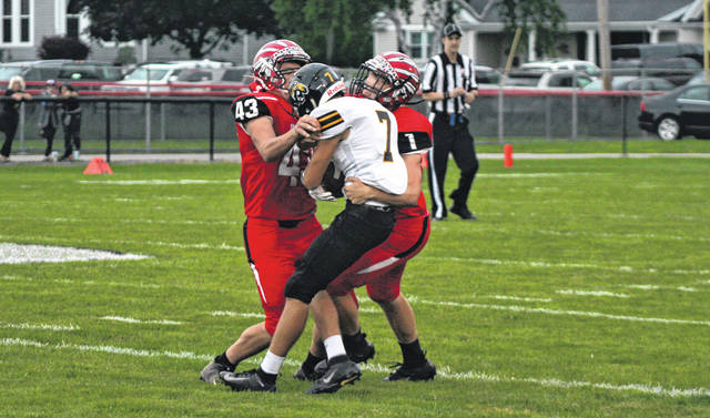 Isaac Wilson of Wauseon, left, and Tyson Britsch combine to stop Fairview's Doug Rakes (7) during Friday's football season opener. The Indians fell in an entertaining game, 34-30.