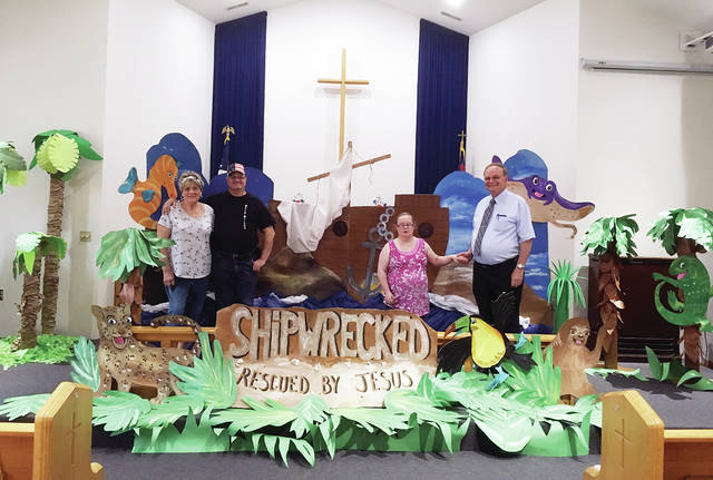 QRC's Activities Center participants gave their time and talent by creating the artwork for the Stryker United Brethren Church's Bible School program. Pictured in the church's sanctuary with the completed project are, from left, Bobbi Schlosser, Jerry Spencer, Pam Mann, and Pastor Nick Woodall.