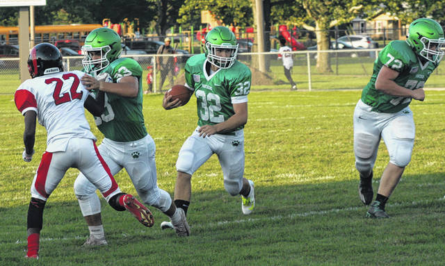 Delta's JD Osborn, center, looks for some running room last Friday versus Toledo Rogers. He had a pair of scores to lead the Panthers to a 20-18 win.